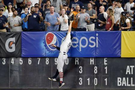 Jul 2, 2018; Bronx, NY, USA; New York Yankees right fielder Aaron Judge (99) is unable to make a catch on a two-run home run by Atlanta Braves left fielder Ronald Acuna Jr. (13) during the eleventh inning at Yankee Stadium. Mandatory Credit: Adam Hunger-USA TODAY Sports