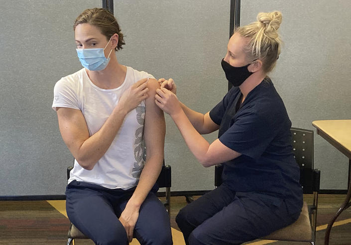 FILE - In this May 10, 2021, file photo, Australian swimmer Cate Campbell receives a Pfizer COVID-19 vaccination at the Queensland Academy of Sport in Brisbane, Australia. Some wealthy nations that were most praised last year for controlling the coronavirus are now lagging far behind in getting their people vaccinated — and some, especially in Asia, are seeing COVID-19 cases grow. (AP Photo/John Pye, File)