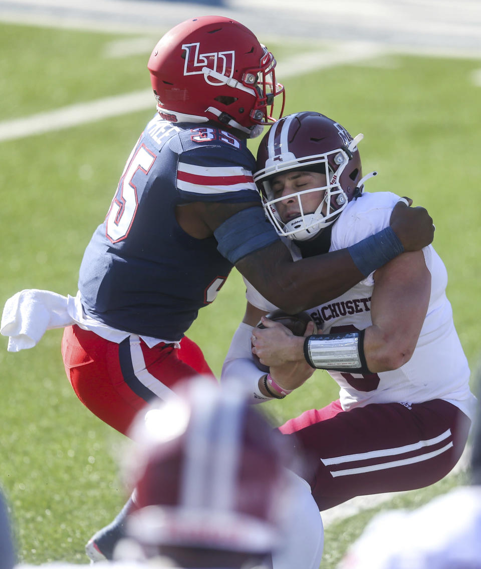 Massachusetts quarterback Garrett Dzuro (9) carries the ball as he is stopped by Liberty linebacker Tyren Dupree (35) during the first half of an NCAA college football game on Friday, Nov. 27, 2020, at Williams Stadium in Lynchburg, Va. (AP Photo/Shaban Athuman)