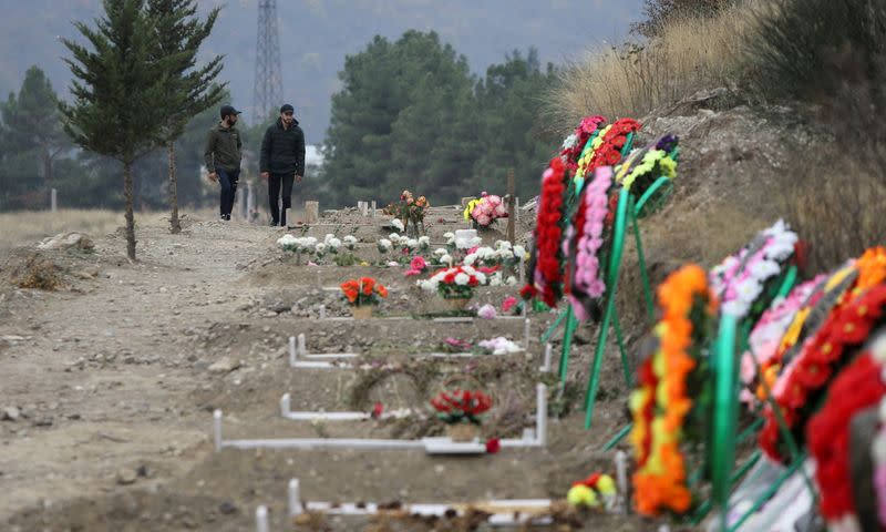 Men walk along graves of soldiers and civilians who were killed during a military conflict over the breakaway region of Nagorno-Karabakh, in Stepanakert