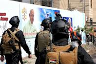 Iraqi security forces patrol around the Cathedral of Saint Joseph during preparations for the Pope's visit in Iraq's capital Baghdad
