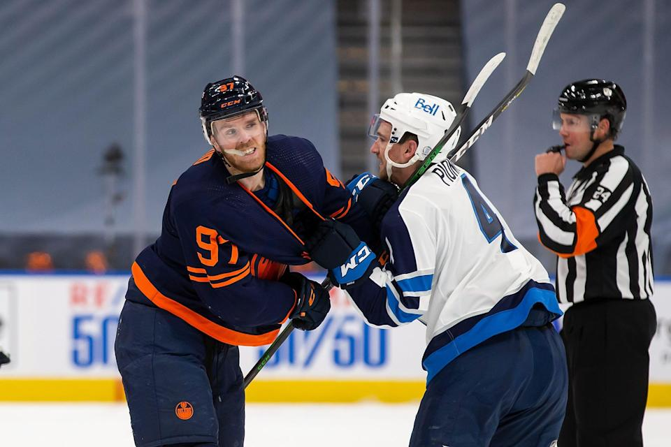 The Oilers' Connor McDavid and Jets' Neal Pionk battle during Game 1.