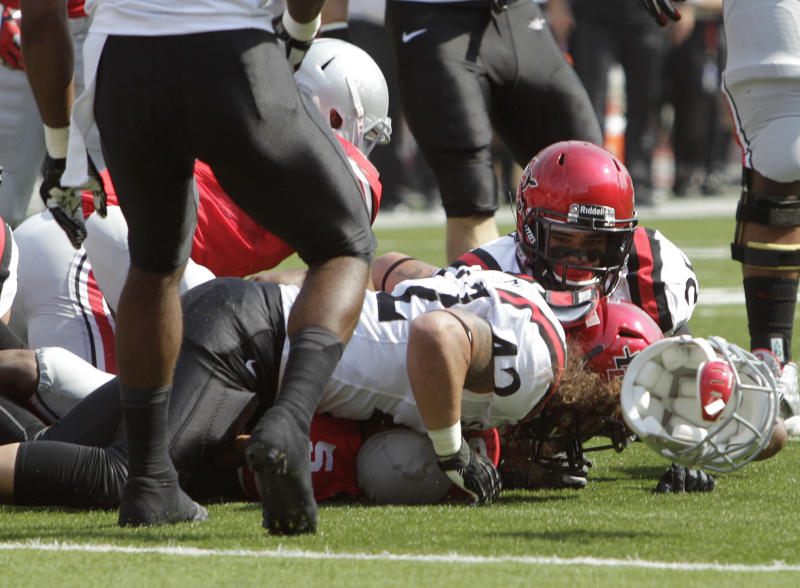 Ohio State quarterback Braxton Miller (5) loses his helmet as he is tackled by San Diego State linebacker Jake Fely during the first quarter of an NCAA college football game Saturday, Sept. 7, 2013, in Columbus, Ohio. (AP Photo/Jay LaPrete)