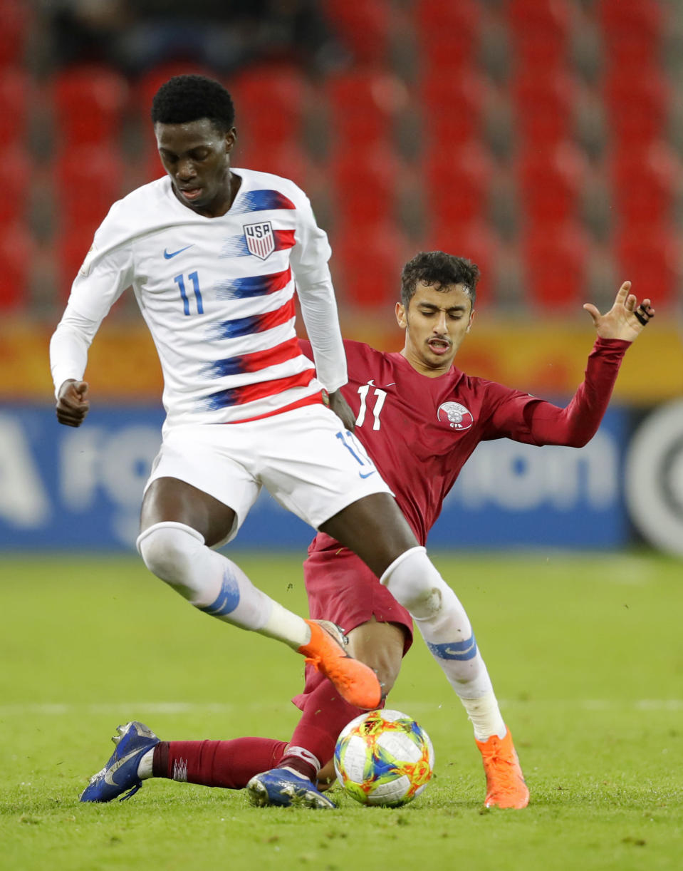 United States' Tim Weah, front, duels for the ball with Qatar's Abdulla Nasser during the Group D U20 World Cup soccer match between USA and Qatar, in Tychy, Poland, Thursday, May 30, 2019. (AP Photo/Sergei Grits)