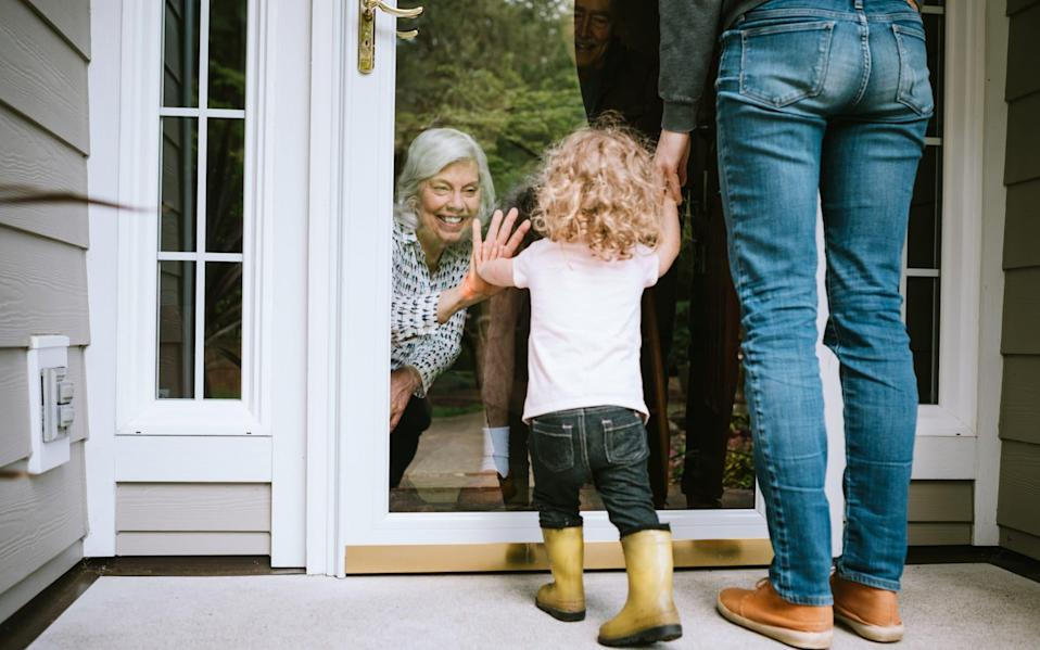 A mother stands with her daughter, visiting senior parents but observing social distancing with a glass door between them - RyanJLane