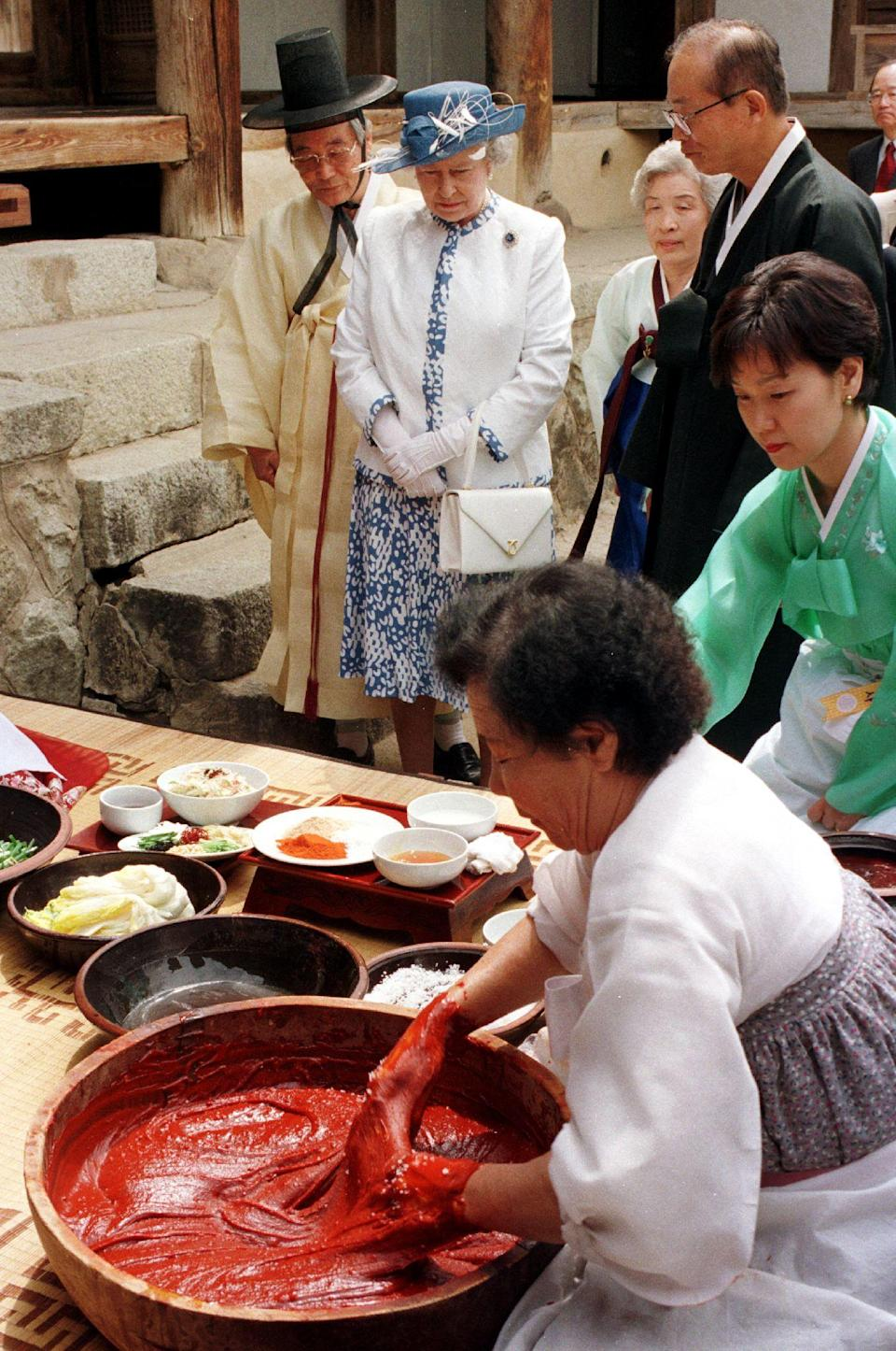 Britain's Queen Elizabeth II (C, top) watches women make South Korean's main side dish Kimchi as she visits a 400-year-old traditional house in the village of Hahoe, Andong province, 268 kilometers southeast of Seoul, 21 April 1999. South Korean aristocrat Ryu Yong-Ha, (R, top) the village chief, who is resisting changes to the country's millenia-old culture, didn not allow the Queen into his main living room which is strictly reserved for men. He disapproved of his relatives' plan to break with tradition and offer the monarch a birthday feast which he views as a demeaning publicity stunt.  AFP PHOTO/CHOO YOUN-KONG (Photo credit should read CHOO YOUN-KONG/AFP via Getty Images)