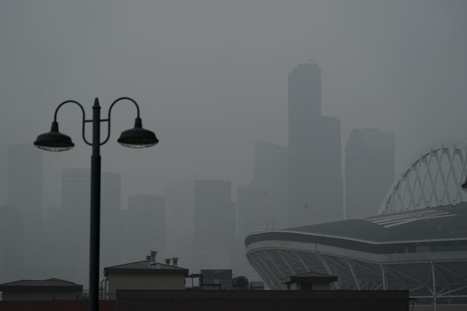 FILE - In this Sept. 14, 2020, file photo, downtown Seattle is barely visible through wildfire smoke, Wednesday, Oct. 14, 2020, near CenturyLink Field, right, as viewed from an upper deck of T-Mobile Park, home of the Seattle Mariners baseball team. Wildfires churning out dense plumes of smoke as they scorch huge swaths of the U.S. West Coast have exposed millions of people to hazardous pollution levels, causing emergency room visits to spike and potentially thousands of deaths among the elderly and infirm, according to an Associated Press analysis of pollution data and interviews with physicians, health authorities and researchers. (AP Photo/Ted S. Warren, File)