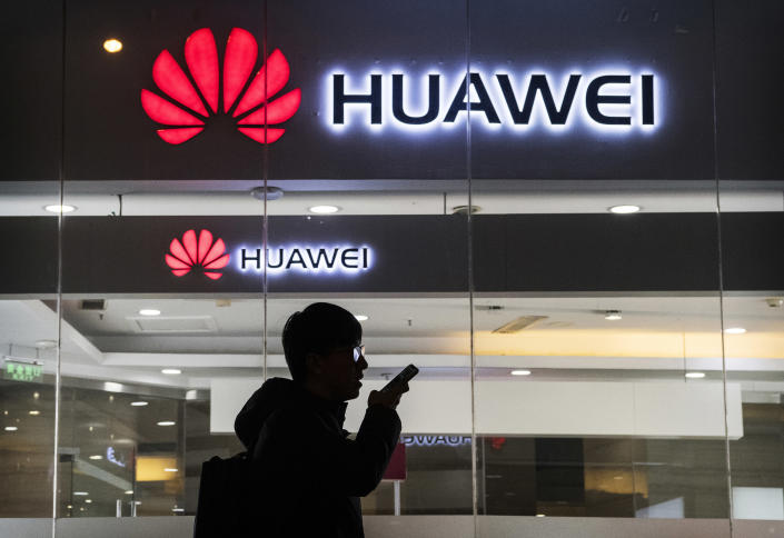 A pedestrian talks on the phone outside a Huawei store in Beijing. (Photo: Kevin Frayer/Getty Images)