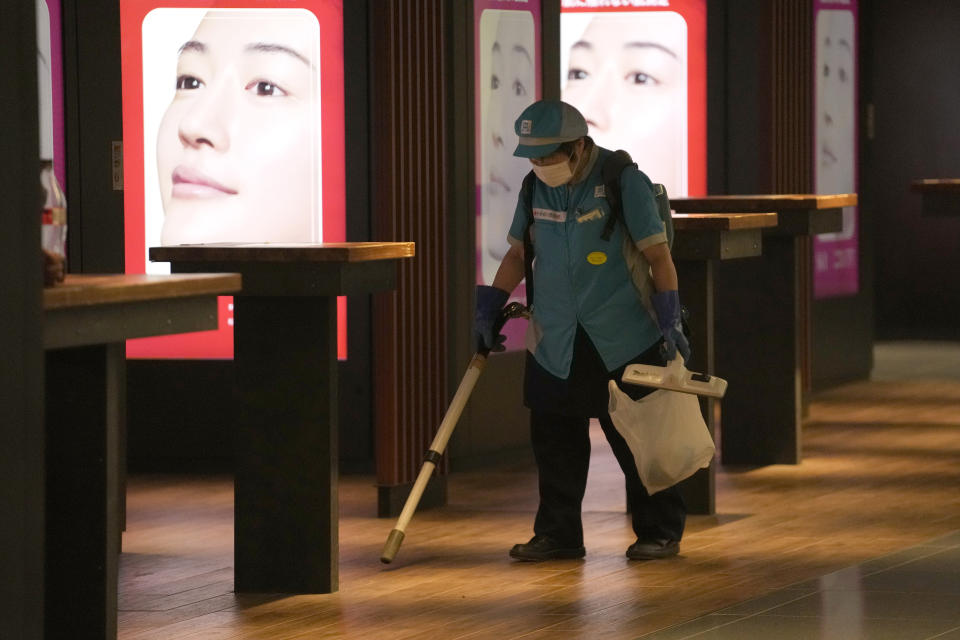 An employee wearing a protective mask to help curb the spread of the coronavirus cleans the floor at the underneath of a subway station Thursday, July 29, 2021, in Tokyo. (AP Photo/Eugene Hoshiko)
