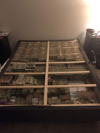 Approximately $17 million found under a mattress in connection with an investigation related to what authorities say was a pyramid scheme is shown in this photo from a January 2017 raid in Westborough, Massachusetts, U.S. released on March 7, 2017.   Courtesy U.S. Attorney's Office in Boston/Handout via REUTERS
