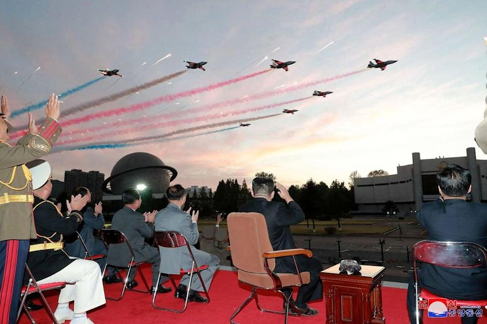 This picture taken on 11 October 2021 and released from North Korea's official Korean Central News Agency shows Kim Jong Un (2nd-R) watching a demonstration flight during the opening ceremony of the defence development exhibition (AFP via Getty Images)