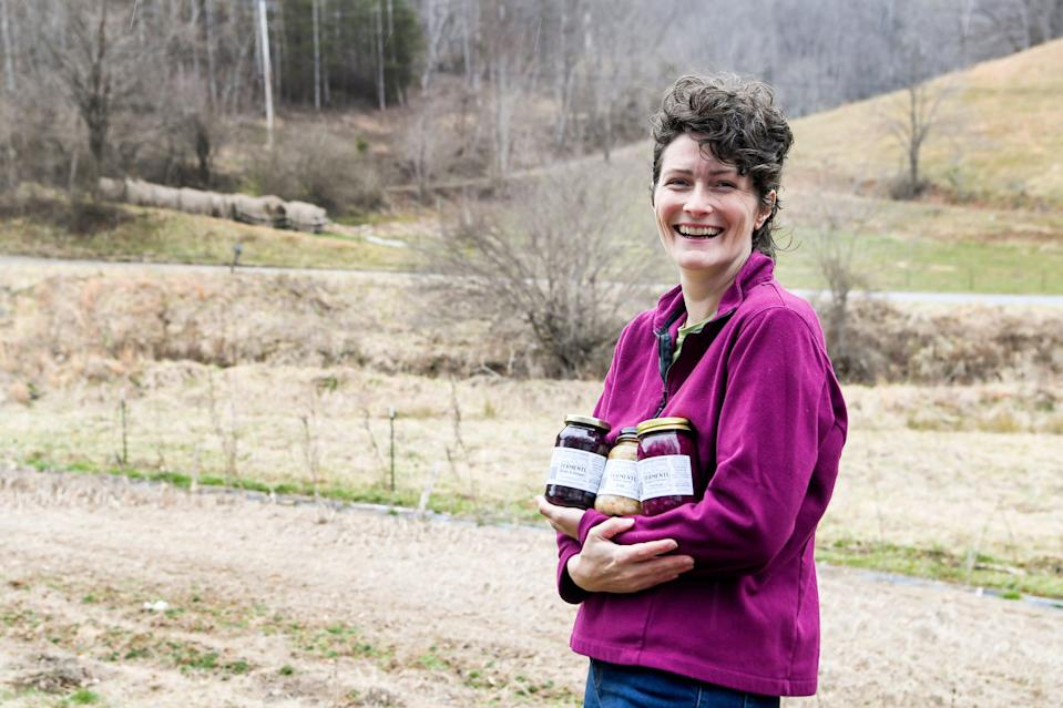 Meg Chamberlain holds jars of her fermented produce next to her field in Marshall, N.C., on Feb. 26.