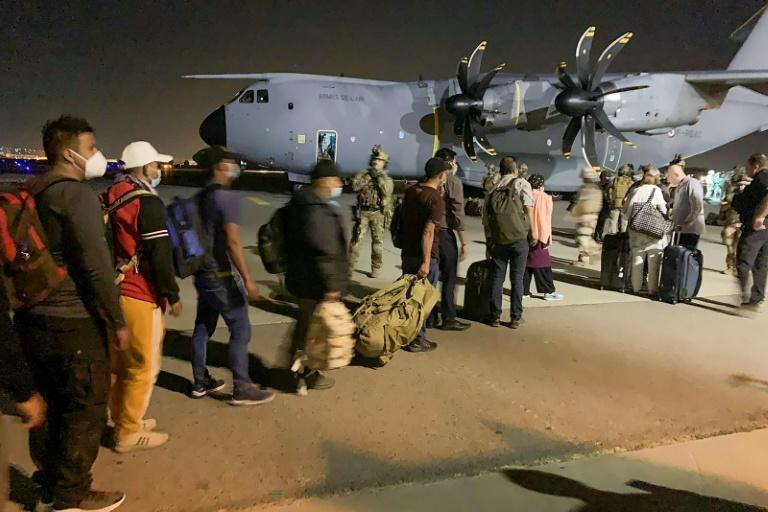 People line up to board a French military transport plane at the Kabul airport on August 17, 2021, for evacuation from Afghanistan after the Taliban's stunning military takeover of the country (AFP/STR)