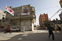 "In this photo taken Friday, May 24, 2013, Palestinians walk by a poster of a Palestinian singer Mohammed Assaf hanging on his family house in Khan Younis, southern Gaza Strip. The 23-year-old wedding singer from the refugee camp has given Palestinians are rare sense of pride and national unity after he reached the finale of ""Arab Idol,"" a regional TV singing contest watched by millions of people. (AP Photo/Adel Hana)"