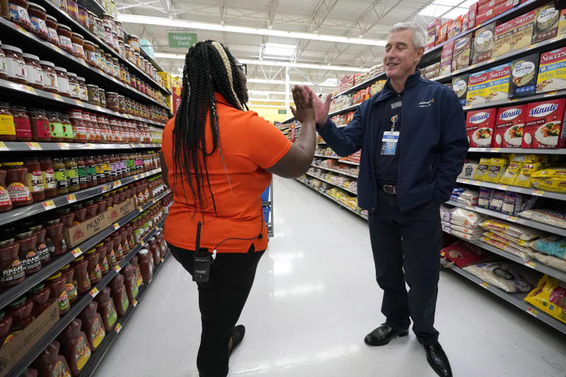 In this Friday, Nov. 9, 2018, photo Walmart U.S. President and CEO Greg Foran, right, high-fives associate Alicia Carter as she fulfills online grocery orders at a Walmart Supercenter in Houston. Foran took over as CEO of the discounter's U.S. division four years ago. (AP Photo/David J. Phillip)
