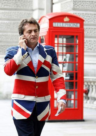 FILE PHOTO: A man wears a Union flag jacket as he passes a traditional red telephone box near to the London 2012 Olympic Games Beach Volleyball Stadium in London July 30, 2012. REUTERS/Luke MacGregor/File Photo
