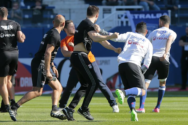 Lyon staff members try to stop a Bastia supporter who invaded the pitch to fight with Lyon players during warm up prior to the French L1 Football match between Bastia (SCB) and Lyon (OL) on April 16, 2017, at the Armand Cesari stadium, in Bastia, on the French Mediterranean island of Corsica. / AFP PHOTO / PASCAL POCHARD-CASABIANCA