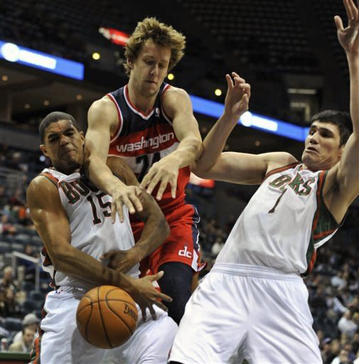 Milwaukee Bucks' Tobias Harris (15) and Ersan Ilyasova fight for the loose ball with Washington Wizards' Jan Vesely during the first half of an NBA basketball game, Saturday, Oct. 20, 2012, in Milwaukee. (AP Photo/Jim Prisching)