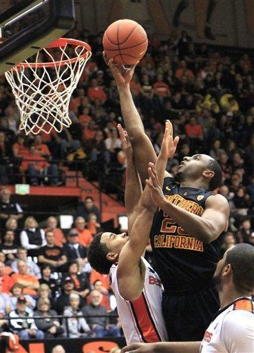 Southern California guard Byron Wesley, right, goes to the basket against Oregon State guard Jared Cunningham during the first half of an NCAA college basketball game in Corvallis, Ore., Saturday, Jan. 21, 2012. (AP Photo/Don Ryan)