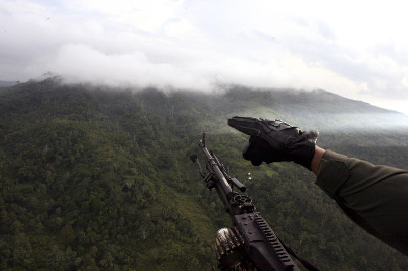 A Philippine Air Force helicopter gunner points to a forested area in Patikul township on southern Jolo island of Sulu province in southern Philippines, Saturday July 30, 2011. Military officials said Friday that al-Qaida-linked Abu Sayyaf militants beheaded two of the seven marines they killed in Thursday's clash with government troops in the island of Jolo. (AP Photo/Al Jacinto)