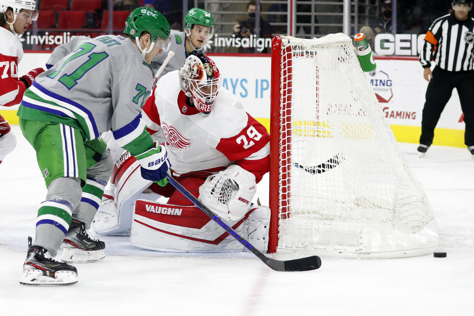 Carolina Hurricanes' Jesper Fast (71) and Detroit Red Wings goaltender Thomas Greiss (29) watch the rebounding puck during the second period of an NHL hockey game in Raleigh, N.C., Saturday, April 10, 2021. (AP Photo/Karl B DeBlaker)