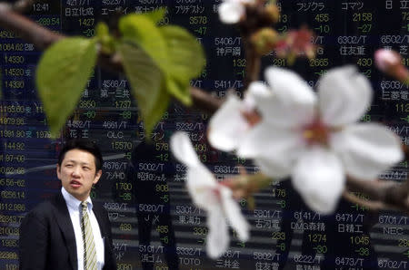 Man walks past an electronic stock quotation board, as cherry blossoms bloom, outside a brokerage in Tokyo
