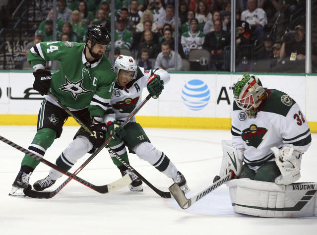 Dallas Stars left wing Jamie Benn (14) shoots against Minnesota Wild goaltender Alex Stalock (32) as defenseman Jared Spurgeon (46) guards in the first period of an NHL hockey game Saturday, April 6, 2019, in Dallas. (AP Photo/Richard W. Rodriguez)