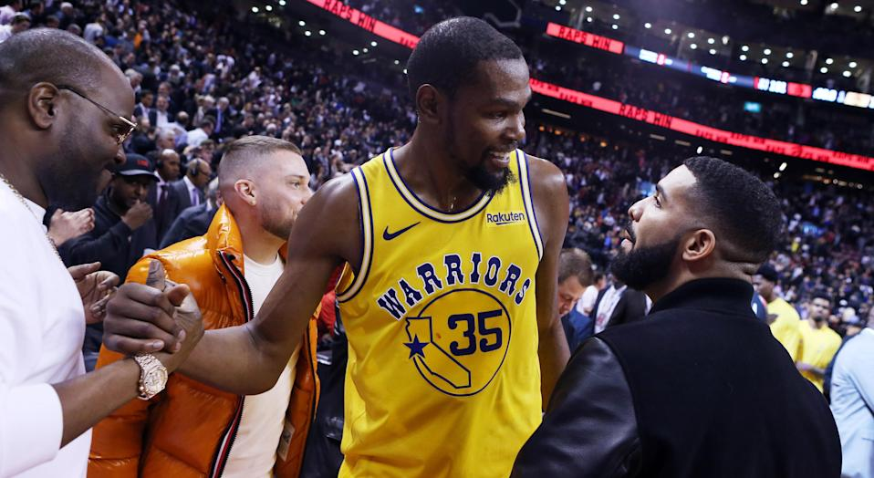 Despite his team's loss to the Raptors, it's nice that Drake could give Kevin Durant a reason to smile. (Photo by Vaughn Ridley/Getty Images)