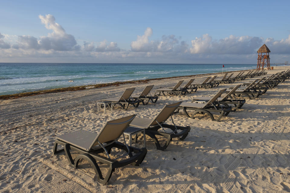 Lounge chairs fill an empty beach in Cancun, Mexico, Thursday, June 11, 2020. An irony of the coronavirus pandemic is that the idyllic beach vacation in Mexico in the brochures really does exist now: the white sand beaches are sparkling clean and empty on the Caribbean coast. (AP Photo/Victor Ruiz)