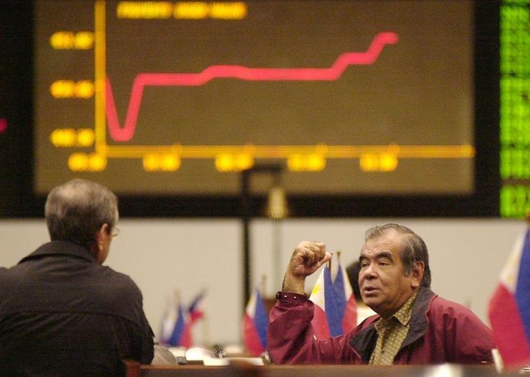 Traders at the Manila Stock Exchange chat in front of an electronic board on January 31, 2003. Asian markets were mixed following another strong lead from Wall Street, where traders took heart from more upbeat US jobs numbers