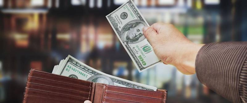 Isolated of hands taking out cash to spend