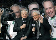 FILE - In this March 16, 2011, file photo, Boston Celtics broadcasters Tommy Heinsohn, left, and Mike Gorman speak on camera as fans wearing photos of the broadcasters' faces stand behind the two, prior to an NBA basketball game between the Celtics and the Indiana Pacers in Boston. The two were celebrating 30 years as a broadcast tandem. Tommy Heinsohn, who as a Boston Celtics player, coach and broadcaster was with the team for all 17 of its NBA championships, has died. He was 86. The team confirmed Heinsohn's death on Tuesday, Nov. 10, 2020.(AP Photo/Elise Amendola, File)