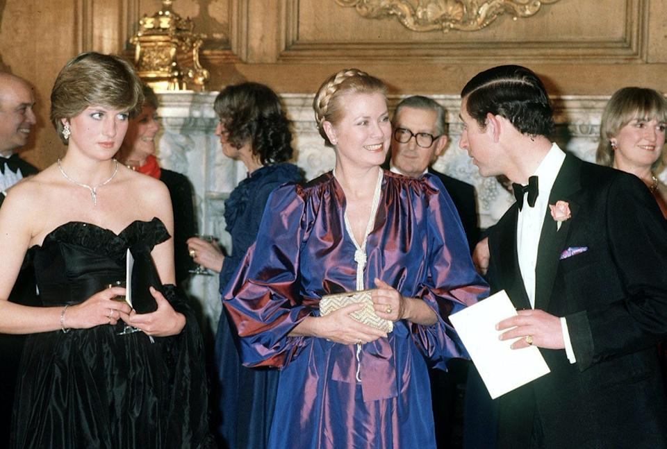 Princess Diana wearing black dress next to Prince Grace of Monaco and Prince Charles in 1982