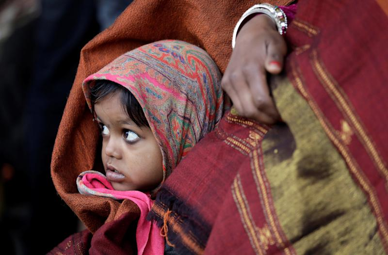 A little girl wrapped in a shawl waits along with her mother at a railway station in New Delhi, India, on the cold winter morning of Jan. 3, 2018. (Saumya Khandelwal / Reuters)