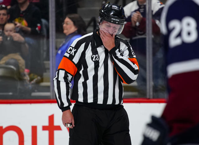 Referee Brad Watson (23) gets emotional during his last game as a referee during the first period of an NHL hockey game between the Colorado Avalanche and the Chicago Blackhawks, Saturday, March 23, 2019 in Denver. (AP Photo/Jack Dempsey)