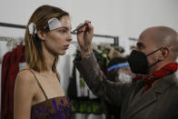 A model gets her make-up done in the backstage prior to the start of the Shi.RT women's Spring-Summer 2021 fashion show, in Milan, Italy, Sunday, Sept. 27, 2020. (AP Photo/Luca Bruno).