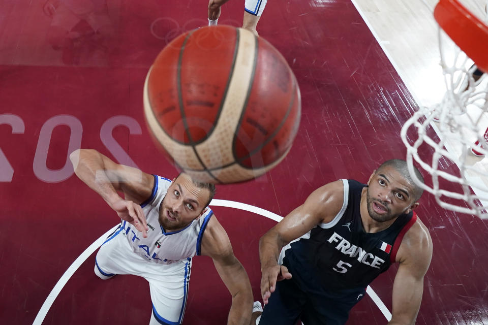 Italy's Stefano Tonut, left, and France's Nicolas Batum (5) battle for a rebound during a men's basketball quarterfinal round game at the 2020 Summer Olympics, Tuesday, Aug. 3, 2021, in Saitama, Japan. (AP Photo/Charlie Neibergall, Pool)