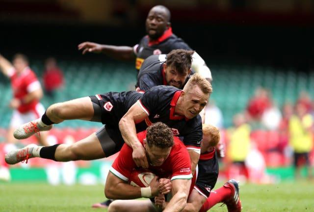 Will Rowlands is tackled by Canada's Peter Nelson