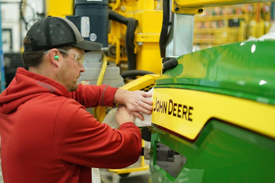 Lance Buhman applies the iconic John Deere decal to the hood of a 7R tractor.