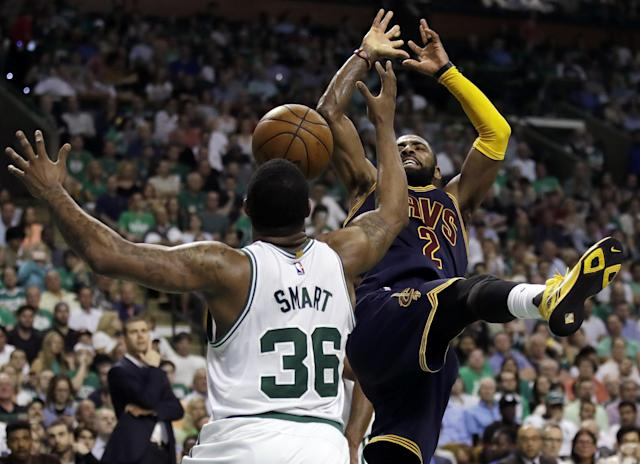 <p>Cleveland Cavaliers guard Kyrie Irving (2) and Boston Celtics guard Marcus Smart (36) vie for a loose ball during the third quarter of Game 1 of the NBA basketball Eastern Conference finals, Wednesday, May 17, 2017, in Boston. (AP Photo/Charles Krupa) </p>