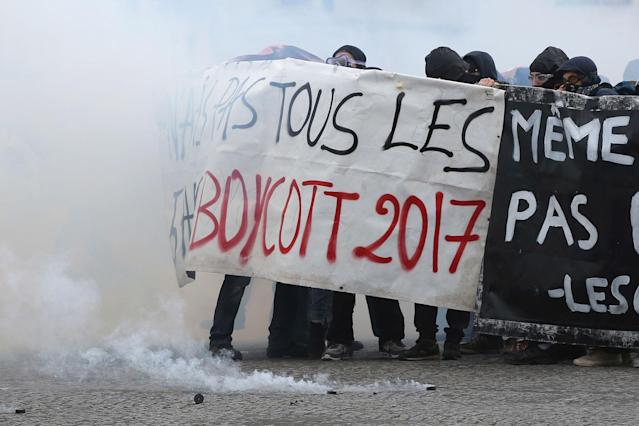 <p>Youths shield behind a banner as Paris police are firing tear gas, during the May Day demonstration, Monday May 1, 2017, in Paris. Scores of hooded youth have thrown Molotov cocktails at security forces who fired back with tear gas during the May Day workers' march in Paris. (AP Photo/Thibault Camus) </p>