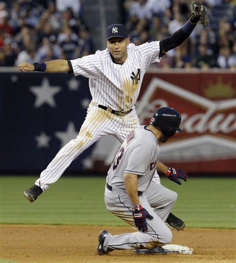 New York Yankees shortstop Derek Jeter, left, leaps to avoid Cleveland Indians' Johnny Damon after forcing out Damon when the Indians' Casey Kotchman hit into a fifth-inning double play during the Yankees' 6-4 win in their baseball game at Yankee Stadium in New York, Tuesday, June 26, 2012. (AP Photo/Kathy Willens)