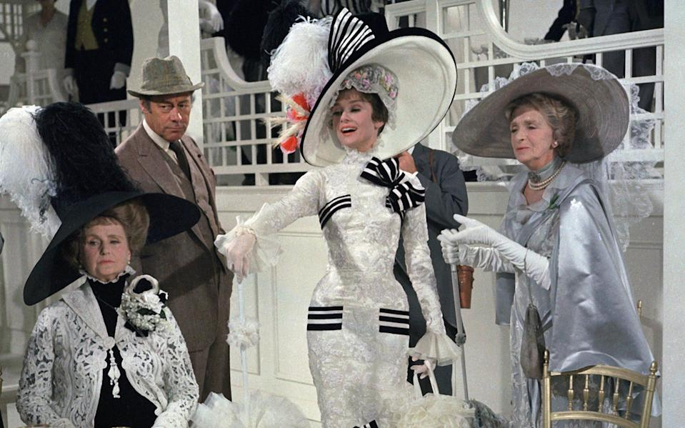 "Audrey Hepburn as Eliza Doolittle (center in white dress) and Rex Harrison, (standing atl eft) as Professor Henry Higgins, in ""My Fair Lady"" - Getty"
