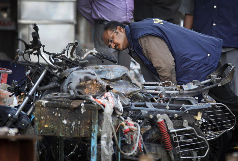 An official of India's National Investigation Agency looks for evidence in the debris at one of the two bomb blast sites, in Hyderabad, India, Friday, Feb. 22, 2013. A day after two bicycle bombs killed more than a dozen people and wounded more than 100, investigators into India's worst bombing in more than a year searched Friday for possible links to anger over the execution of a Muslim militant. (AP Photo/Aijaz Rahi)
