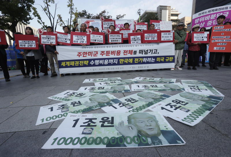 """Fake bank notes showing images of U.S. President Donald Trump are displayed as protesters stage a rally to oppose the United States' demand for raising the defense costs for stationing U.S. troops in South Korea, near the U.S. embassy in Seoul, South Korea, Tuesday, Oct. 22, 2019. South Korean police have formally arrested four anti-American students who broke into the U.S. ambassador's residence in Seoul while protesting the Trump administration's demands for South Korea to pay more to help cover the costs of keeping U.S. troops. The sign reads """"We opposed the U.S. demand for raising defense costs"""" (AP Photo/Ahn Young-joon)"""