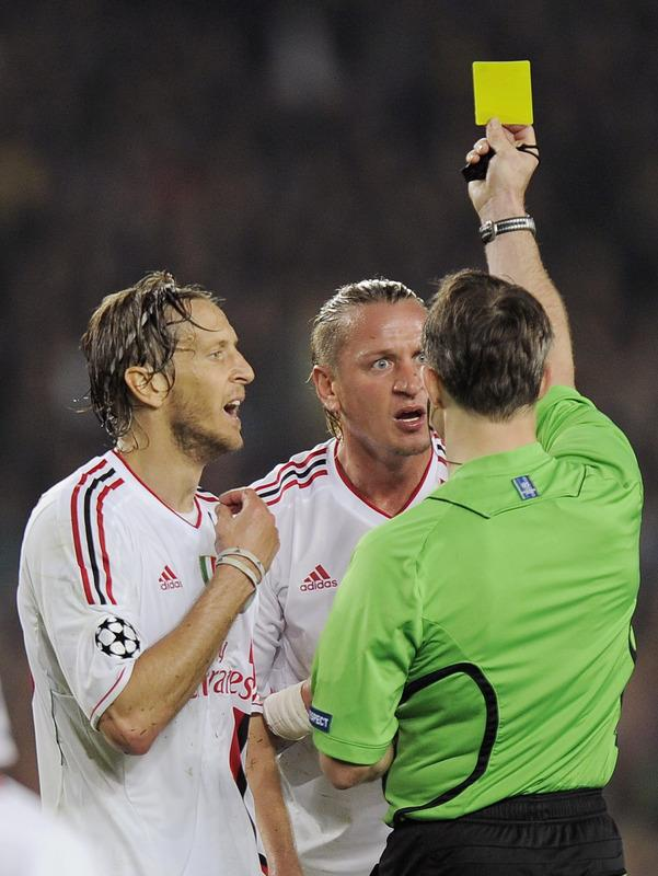 AC Milan's French defender Philippe Mexes(C) gets a yellow card from Dutch referee Bjoern Kuipers during the Champions League quarter-final second leg football match FC Barcelona vs AC Milan on April 3, 2012 at Camp Nou stadium in Barcelona. FC Barcelona defeated AC Milan 3-1 to reach the semi-finals.     AFP PHOTO / LLUIS GENE