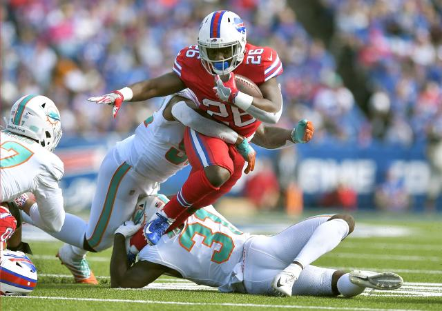 Miami Dolphins linebacker Raekwon McMillan, left, and defensive back Ken Webster, below, tackle Buffalo Bills running back Devin Singletary, center, in the first half of an NFL football game, Sunday, Oct. 20, 2019, in Orchard Park, N.Y. (AP Photo/Adrian Kraus)
