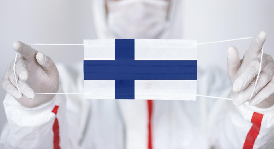 Healthcare personnel is holding Finnish Flag shaped surgical mask.