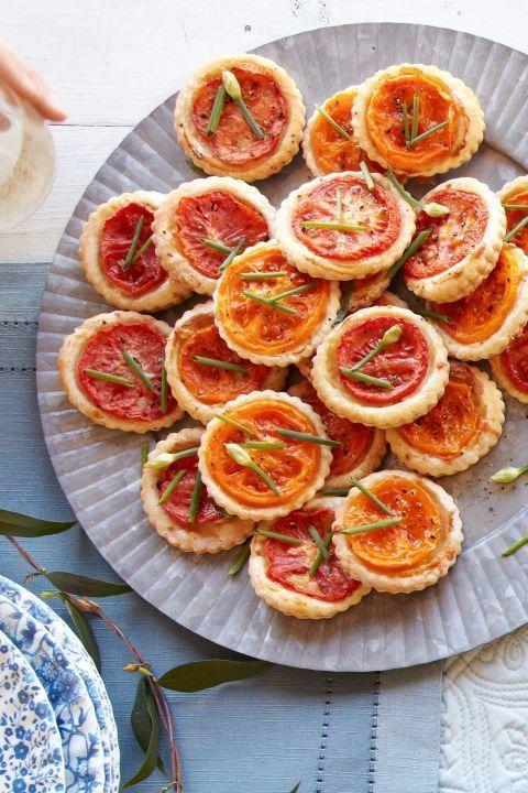 "<p>These bright tartlets cook up quickly and can easily be rewarmed.</p><p><strong><a href=""https://www.countryliving.com/food-drinks/recipes/a38080/tomato-manchego-tartlets-recipe/"" rel=""nofollow noopener"" target=""_blank"" data-ylk=""slk:Get the recipe"" class=""link rapid-noclick-resp"">Get the recipe</a>.</strong></p>"