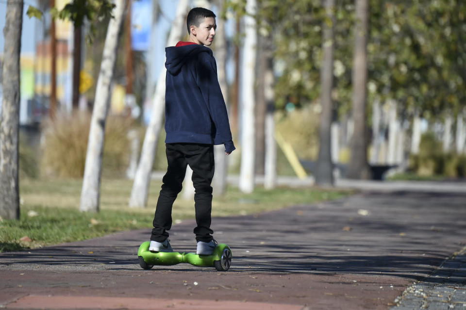 A boy rides a hoverboard on the day after Christmas, in San Pedro, California December 26, 2015. Reports of some hoverboards, also known as self-balancing, two-wheeled scooters catching fire have led to an investigation by the Consumer Product Safety Commission.  AFP PHOTO / ROBYN BECK / AFP / ROBYN BECK        (Photo credit should read ROBYN BECK/AFP via Getty Images)